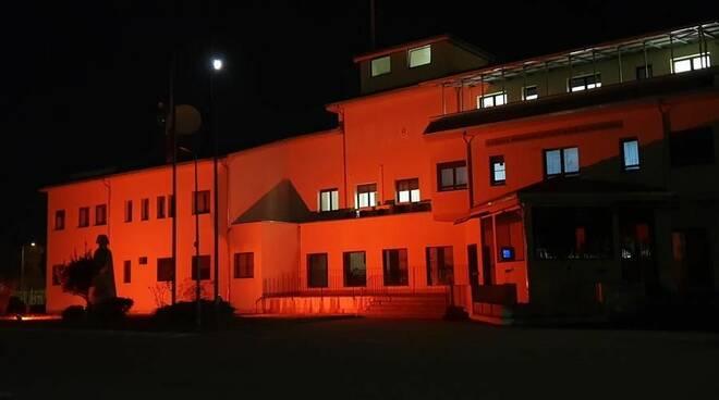 Una caserma dei Carabinieri illuminata di arancione per il 25 novembre.